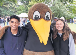 Kandoo mascot with arms around two students