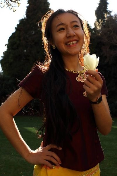 Christine smiling and holding a flower