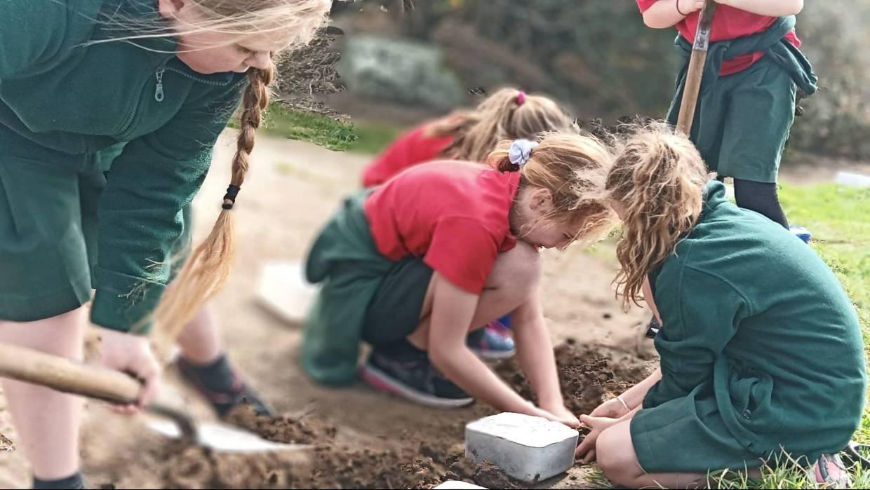 group of kids digging mud