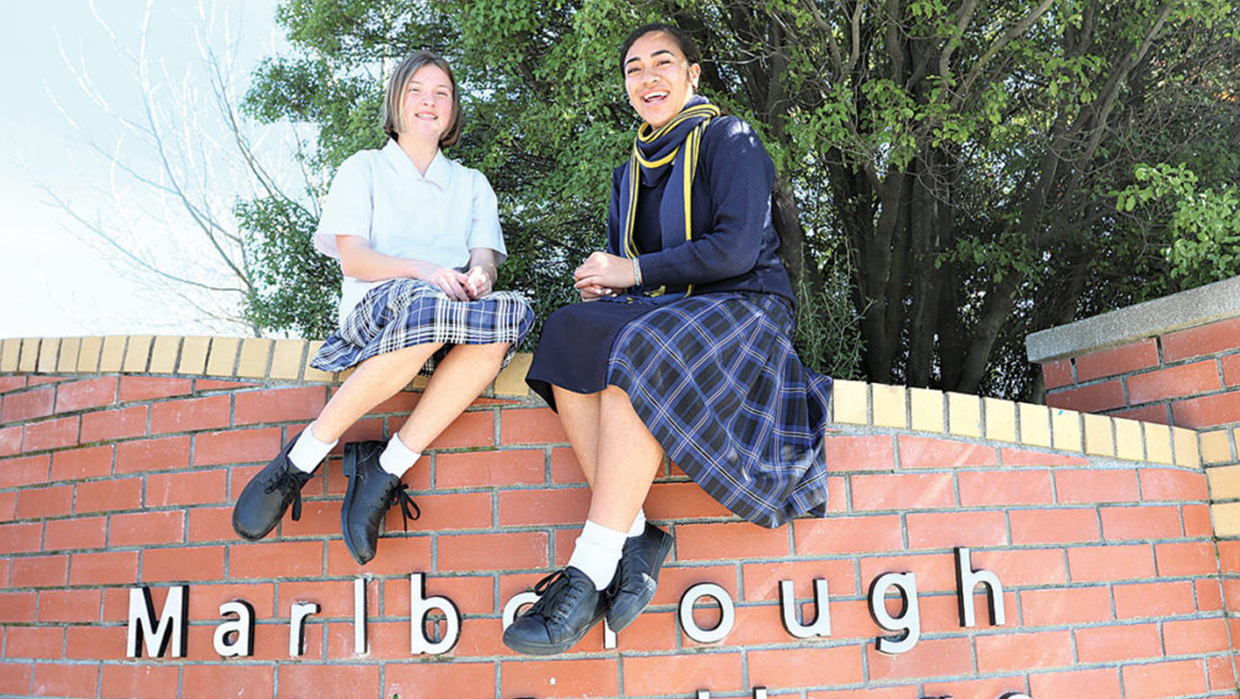 two students sitting on fence smiling