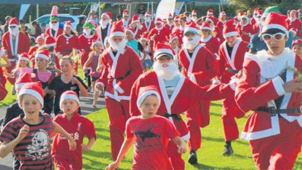 Kids dressed in Santa costumes running