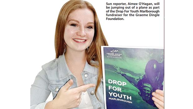 Aimee O'Hagan smiling poiting at Drop for Youth poster
