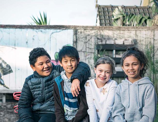 Four kids sitting on bench